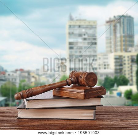 Judge's gavel with books on cityscape background. Concept of law