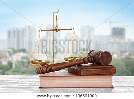 Judge's gavel with book and scales on cityscape background. Concept of law