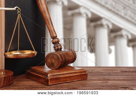 Judge's gavel with scales and courthouse on background. Concept of law