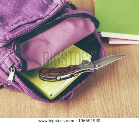 Backpack with knife on school desk in classroom, closeup