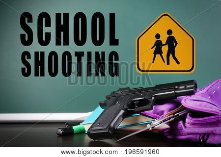 Backpack with gun and knife on table against blackboard. School shooting concept
