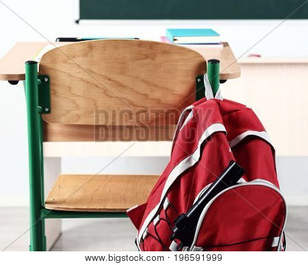 Backpack with gun hanging on chair in classroom. School shooting concept