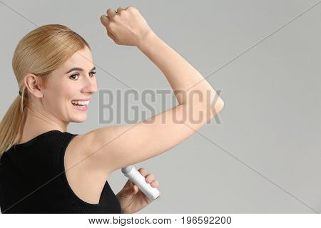 Beautiful young woman using deodorant on light background