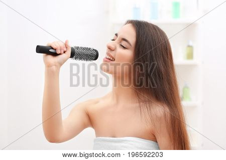 Young emotional woman singing in bathroom after shower