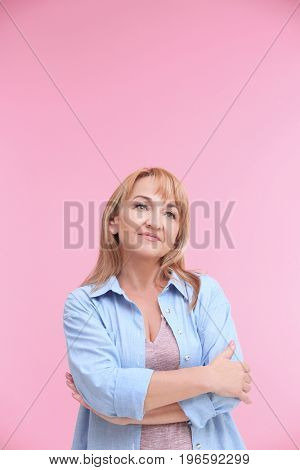 Portrait of attractive mature woman on color background