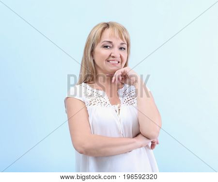Portrait of  mature woman on light blue background