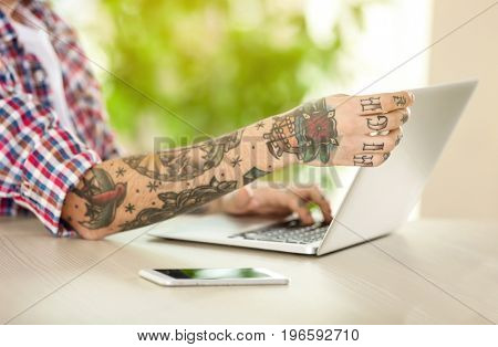 Man using laptop for browsing internet store at table, closeup. Online shopping concept