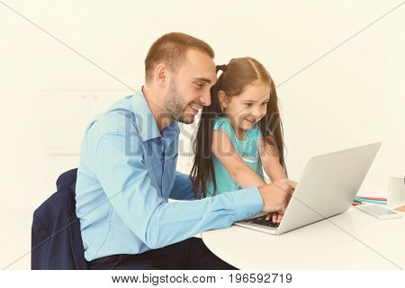Father and daughter using laptop for browsing internet store at home. Online shopping concept