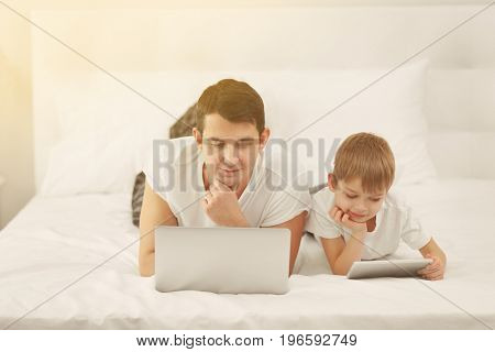 Father with son using laptop and tablet for browsing internet store at home. Online shopping concept