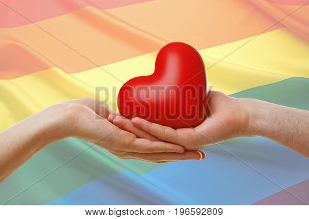 Gay couple holding red heart and LGBT flag on background