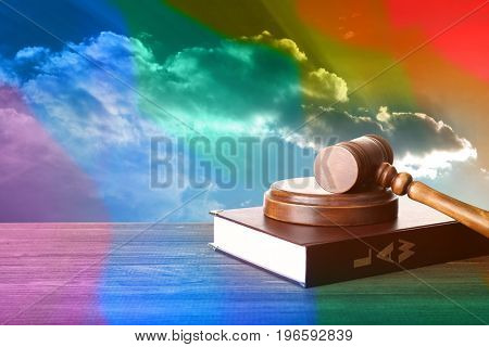 Judge's gavel and book on wooden table against sky background. Gay rights concept