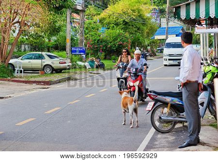 PHUKET ISLAND, THAILAND - OCTOBER 12, 2009: Man and woman rides on a scooter through the streets on Surin beach in Phuket