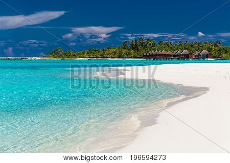 Over water villas in Maldives and a white sandy beach with palm trees