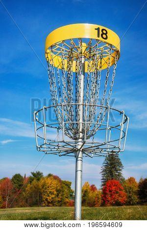 Disc golf target against blue sky in autumn