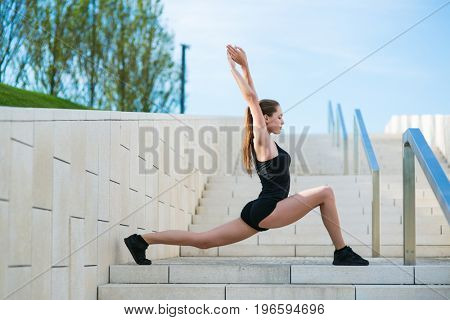 Beautiful young woman doing sports exercises in the park