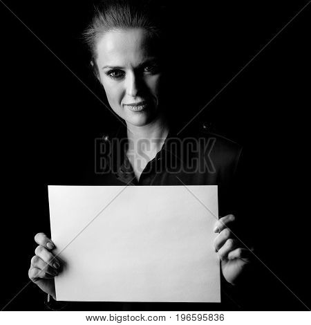 Woman Isolated On Black Background Showing Blank Paper Sheet