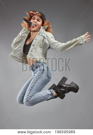 Female singer jumping isolated on grey background