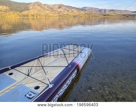 Fort Collins, CO, USA - July 23, 2016: Expedition stand up paddleboard by Starboard on a mounbtain lake (Horsetooth Reservoir).
