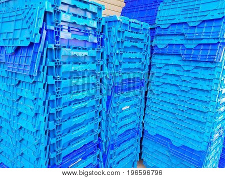 Blue plastic bins stacked high outside a store