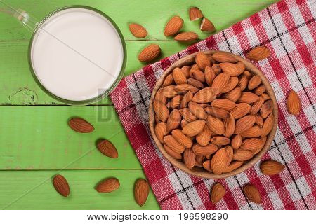 Almond milk in a glass and almonds in a bowl on green wooden background. Top view.