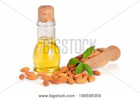 Bottle of almond oil and almonds with leaf in a wooden scoop isolated on white background.