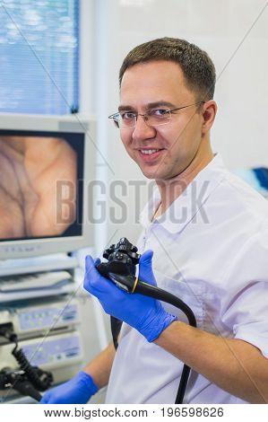 proctologist doctor holding Ligador hemorroidal in office.