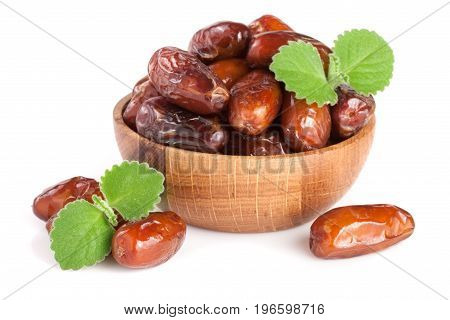 Dates in a wooden bowl with a mint leaf isolated on white background.