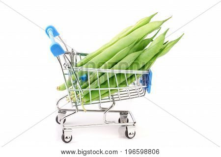 Green beans in mini shopping cart isolated on a white background.