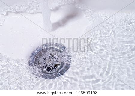 Water running down in the drain. Bathroom sink close up