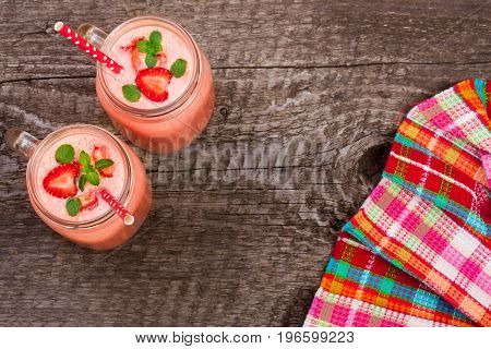 Glass of strawberry smoothie with mint leaves on an old wooden background with a tablecloth with copy space for your text. Top view.