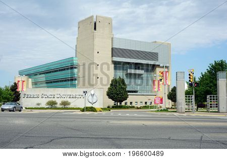 BIG RAPIDS, MICHIGAN / UNITED STATES - MAY 22, 2017: The Ferris State University Library for Information Technology and Education stands behind the iconic Ferris State University sign on Perry Street.
