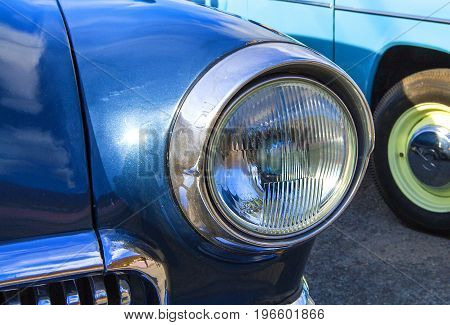 Blue vintage car on a festival of old cars. Retro car's headlight close up.