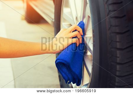 Women's hand wiping blue cloth on alloy Wheels.