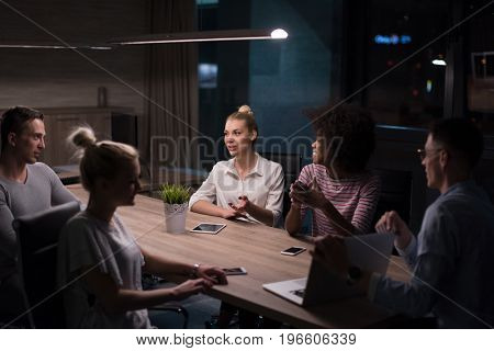 Multiethnic startup business team on meeting in modern night office interior brainstorming, working on laptop