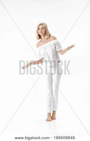 Beautiful happy blond woman in a white blouse and pants on a white background