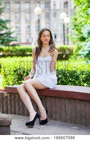 Beautiful young brunette woman reading a message on the phone, summer outdoors