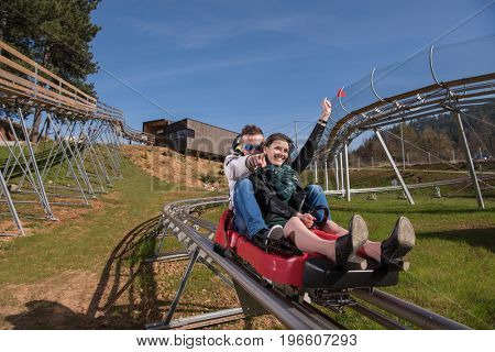 Excited young couple enjoys driving on alpine coaster