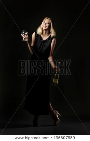 Beautiful drunk blonde woman holding a white wine bottle on a black background. Party and holiday