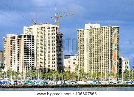 Honolulu, Hawaii, USA - May 30, 2016: High rise buildings tower behind yachts moored at the Ala Wai Yacht Club at Ala Moana.
