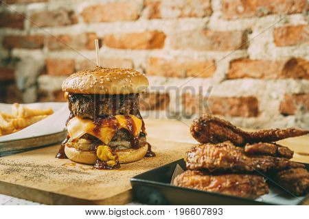 Homemade double cheese and beef burgers with deep fried chicken wing and french fries on the wooden table