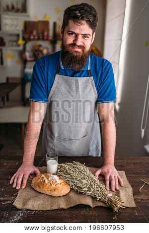Baker against bread, wheat, milk on burlap cloth