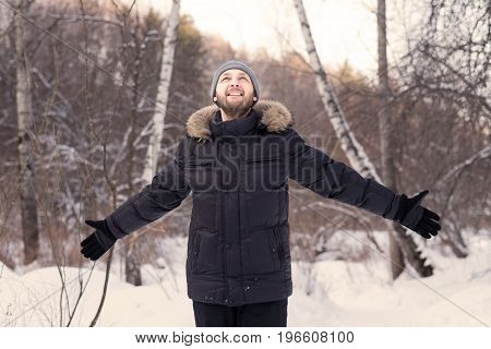 Young happy man with wide open arms in a winter forest.