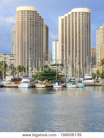 Honolulu Hawaii USA - May 30 2016: Yachts docked at Ala Wai Boat Harbour in the Kahanamoku Lagoon against High Rise buildings in the background.