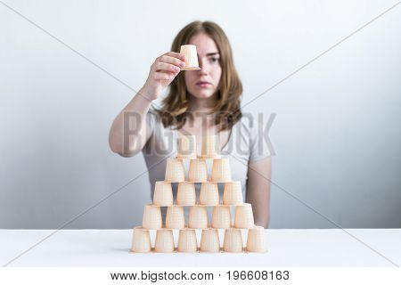 Woman making a pyramid from little plastic glasses. Focus is on a pyramid.
