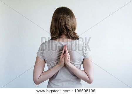 Concept of flexibility. Woman with her hands laying together behind her back.