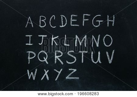 Alphabet letters written in chalk on blackboard