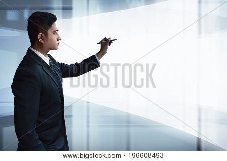 Businessman drawing on virtual screen in office