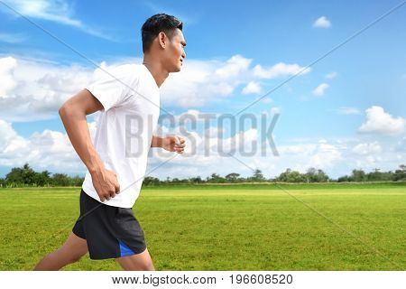 Asian man running on meadow field to training