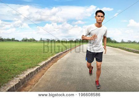 Asian man running on asphalt road to training