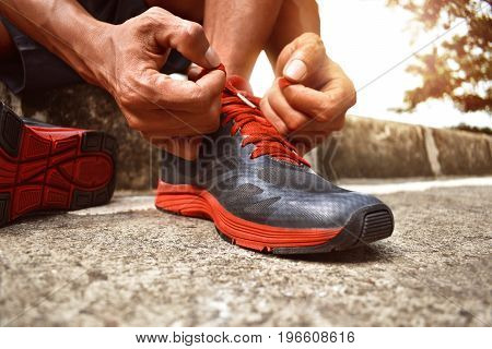 Man tying running shoes prepare to race